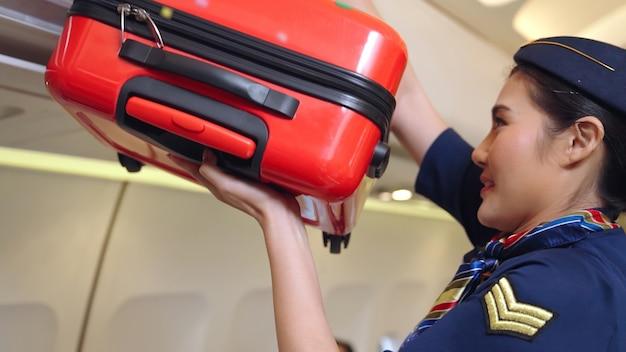 Bagagli dell'ascensore dell'equipaggio di cabina in aereo. trasporto aereo e concetto di turismo.