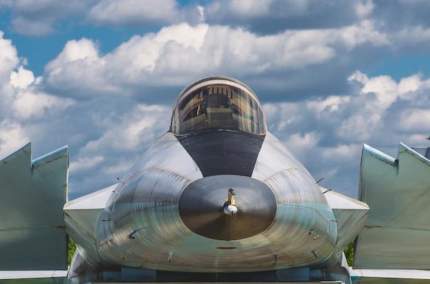 Vecchio combattente pilota di cabina contro il cielo e le nuvole.