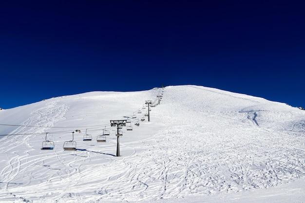 Funivia tra le montagne innevate e il cielo blu profondo chiaro