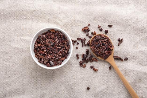 Pennini di cacao in ciotola bianca e cucchiaio di legno sul tavolo