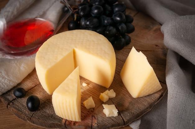 Caciotta su tavola di legno tonda. avvicinamento. nelle vicinanze si trovano diverse fette di formaggio e uva nera. in fondo è un bicchiere di vino rosso. tessuto di lino grigio di sfondo.