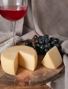 Caciotta su tavola di legno tonda. accanto a un pezzo di formaggio a fette, uva nera e un bicchiere di vino rosso. tessuto di fondo grigio di lino.