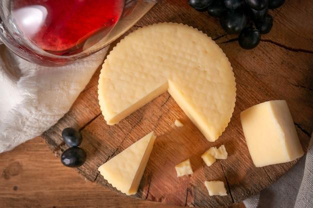 Caciotta su tavola di legno tonda. vista dall'alto. nelle vicinanze si trovano diverse fette di formaggio e uva nera. in fondo è un bicchiere di vino rosso. tessuto di lino grigio di sfondo.