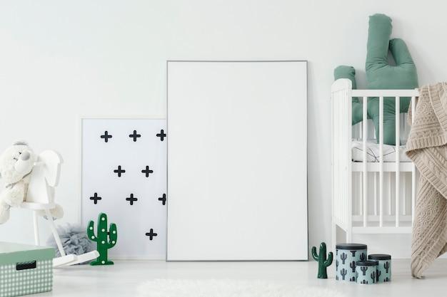Cuscino di cactus in culla bianca accanto a poster vuoto con mockup all'interno della stanza del bambino. foto reale con un posto per il tuo design grafico