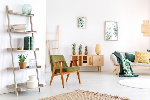 Cactus sullo scaffale in sala relax con poltrona verde e ananas su credenza rustica