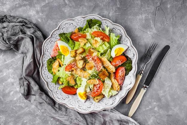 Caesar salad con pollo su un bel piatto e vista dall'alto di sfondo grigio cemento.