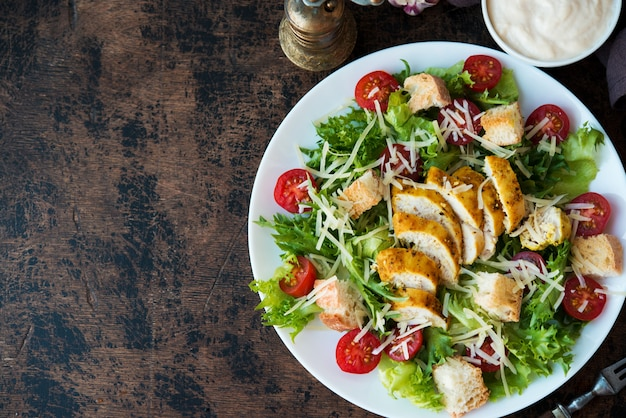 Insalata caesar con petto di pollo, crostini e salsa di parmigiano su un tavolo di legno, una copia dello spazio, vista dall'alto