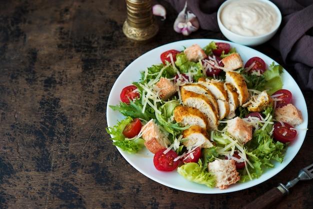 Insalata caesar con petto di pollo, crostini e salsa di parmigiano su un tavolo di legno, uno spazio di copia
