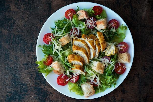 Insalata caesar con petto di pollo, crostini e salsa di parmigiano su un tavolo di legno, vista dall'alto