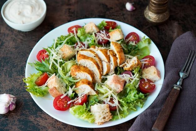 Insalata caesar con petto di pollo, crostini e salsa di parmigiano su un tavolo di legno