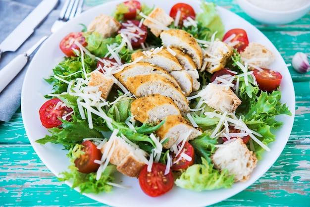 Insalata caesar con petto di pollo su fondo rustico, pomodori, parmigiano, insalata verde e crostini, fuoco selettivo, primo piano