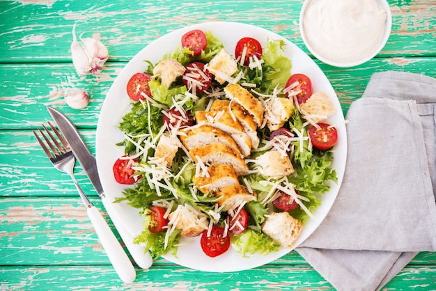 Insalata caesar con petto di pollo su fondo rustico, pomodori, parmigiano, insalata verde e crostini, fuoco selettivo, vista dall'alto