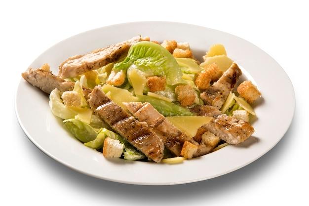 Caesar salad con crostini di pane e pollo alla griglia su superficie bianca.