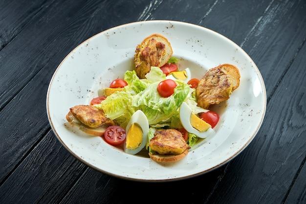 Caesar salad con crostini di pane, parmigiano, pancetta, pollo, uovo in banda nera su fondo di legno.