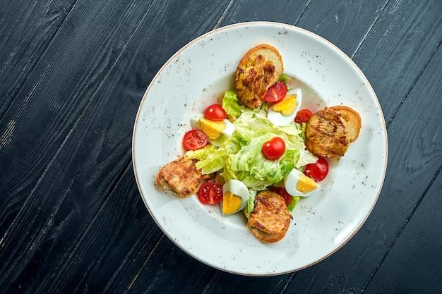 Insalata caesar con crostini di pane, parmigiano, pancetta, pollo, uova in banda nera su superficie di legno. servizio ristorante. chiudere con copia spazio.