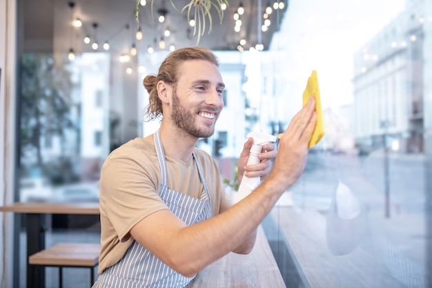 Cafe, pulizia. sorridente giovane uomo barbuto in grembiule tergi finestra nella caffetteria nel pomeriggio di buon umore