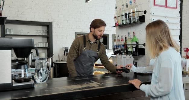 Nel bar l'uomo fa il caffè da asporto per un cliente che paga con carta di credito