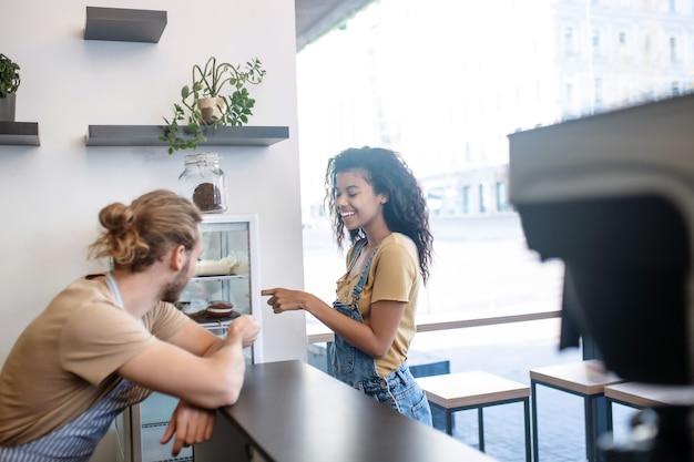 Caffè, ordine. felice donna dai capelli lunghi in tuta di jeans che sceglie la torta vicino al bancone in caffetteria e uomo in grembiule con la schiena