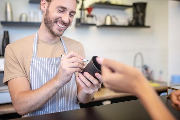 Cafe, servizio. sorridente giovane uomo barbuto in grembiule iscritto con pennarello su vetro in piedi dietro il bancone e la mano della donna