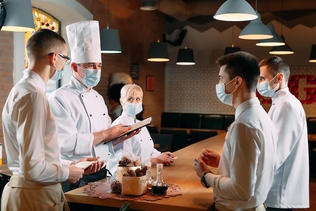 Il personale del bar durante il briefing mattutino indossa maschere protettive.