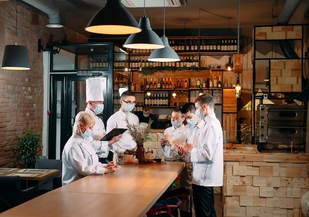 Il personale del bar durante il briefing mattutino indossa maschere protettive