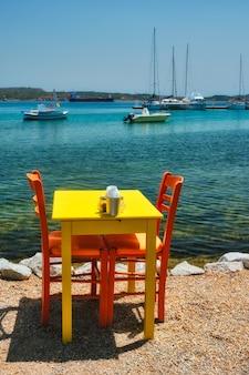 Cafe tableon spiaggia nella città di adamantas sull'isola di milos con il mar egeo con barche in background