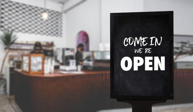 Cameriere di caffè in piedi davanti al negozio di caffè segno retrò vintage apri segno al caffè