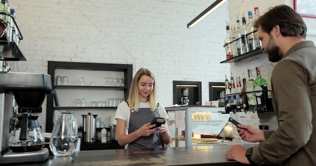 Nella caffetteria la donna prepara il caffè da asporto per un cliente che paga utilizzando il pagamento contactless della carta di credito spendendo denaro al bar con il servizio di transazione digitale.