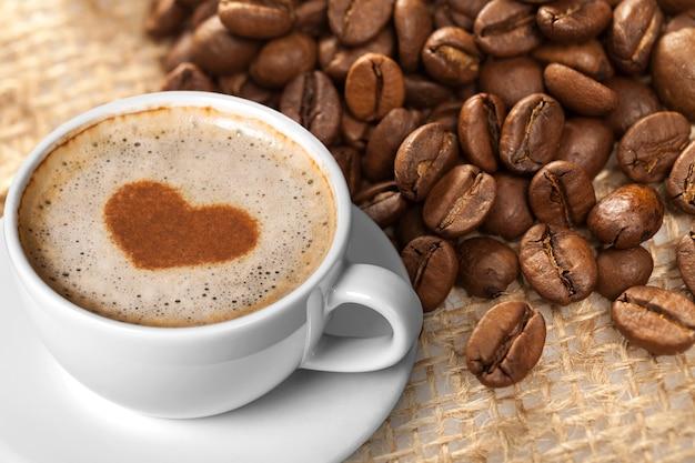 Caffè e ristoranti. una tazza di caffè nero con schiuma e chicchi di caffè.