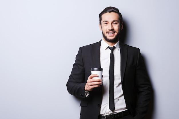Caffeina per la ricarica prima di lavorare. ritratto di giovane fiducioso in abiti da cerimonia che guarda la telecamera e tiene in mano una tazza di caffè mentre si trova in piedi su uno sfondo grigio