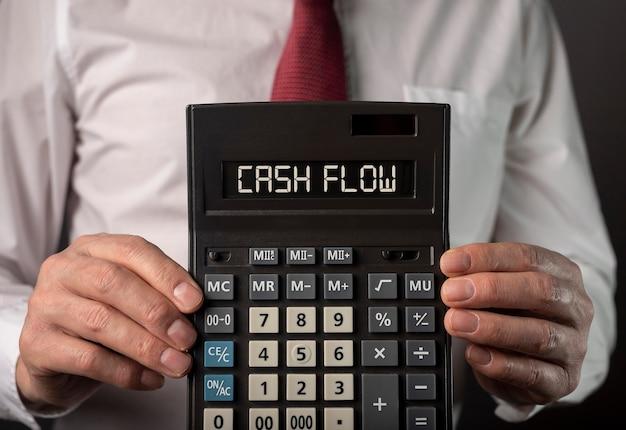 Parole di flusso di cassa sulla calcolatrice nel concetto di flusso di cassa delle mani