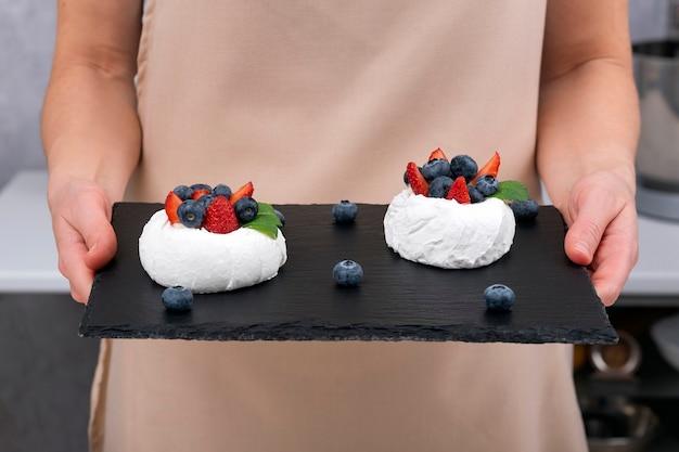 Torta anna pavlova su vassoio nero nelle mani della donna. torta di meringa con frutti di bosco freschi.