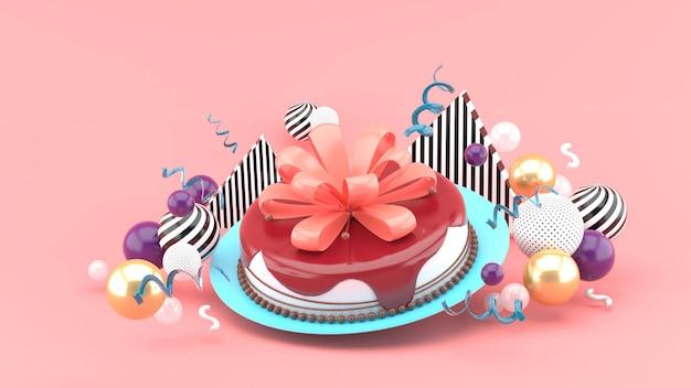 Torta e fiocco tra palline colorate su uno spazio rosa