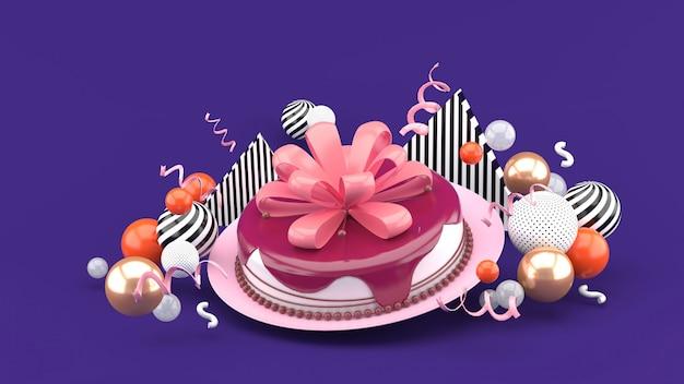 Torta e fiocco tra palline colorate su uno spazio viola