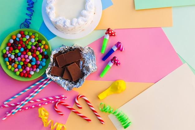Torta, caramelle, cioccolato, fischietti, stelle filanti, palloncini sul tavolo delle vacanze.