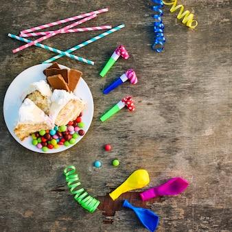 Torta, caramelle, cioccolato, fischietti, stelle filanti, palloncini sul tavolo delle vacanze