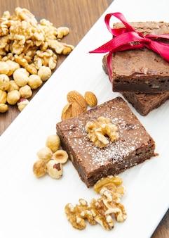 Torta brownies al cioccolato su piatto bianco con noci