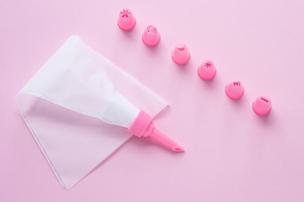 Strumenti per decorare la torta, il sacchetto di pasta con ugelli sul rosa