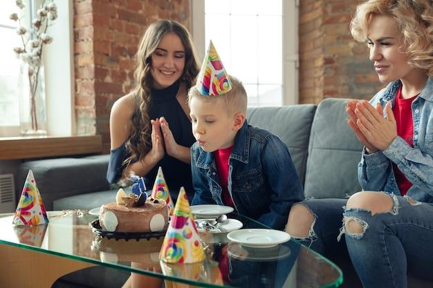 Mangiare la torta. madre, figlio e sorella a casa si divertono. vacanze, famiglia, comfort, concetto accogliente, festeggiare il compleanno. bella famiglia caucasica. trascorrere del tempo insieme, giocare, ridere, salutare