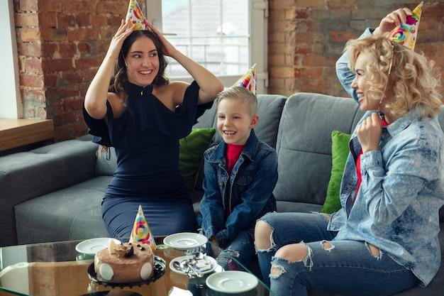 Mangiare la torta. madre, figlio e sorella a casa si divertono