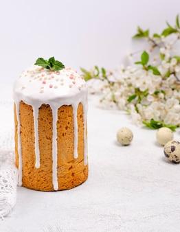 La torta è decorata con glassa di zucchero bianco e granelli di pasta frolla su fondo bianco