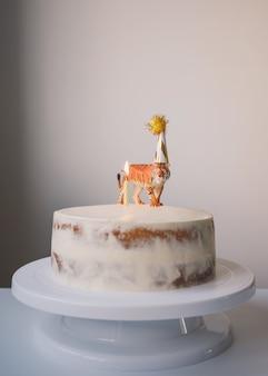 Una torta in stile minimalista con una figurina di una tigre con un cappello da festa compleanno e vacanze