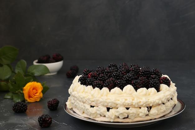 Torta pavlova con more e panna montata, situata su uno sfondo scuro
