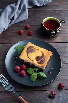 Torta su un piatto di brownie al cioccolato e cheesecake alla ricotta con lamponi.