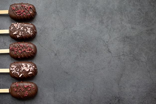 Cake pops in glassa al cioccolato sotto forma di gelato sfondo grigio pietra torta ghiacciolo