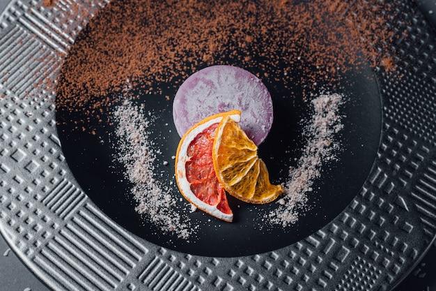 Torta. dessert vegetariano crudo di frutta secca, composizione di noci e cremoso di anacardi, burro di cocco, carruba. sul piatto, isolato su sfondo nero, da vicino