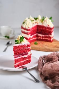Torta di velluto rosso. dessert guarnito con crema di formaggio cremoso e foglie di menta. torta rossa con al centro uno strato di lamponi.