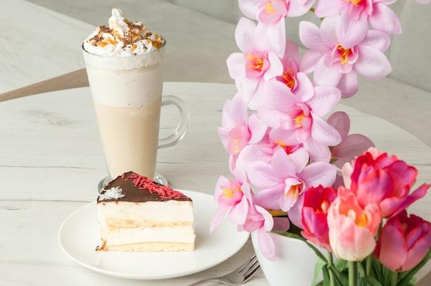 Torta su un piattino e cocktail in un bicchiere alto su un tavolo con fiori