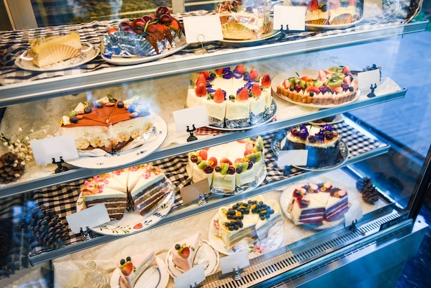 Torta sulla mensola con molte varietà di torta sul negozio di panetteria