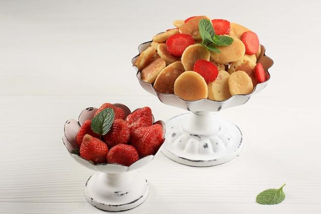 Alzata per torta con piccoli cereali per pancake e fragole, guarnita con foglie di menta su sfondo bianco. cibo alla moda. mini pancake ai cereali. orientamento orizzontale